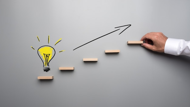 Yellow hand drawn light bulb on the bottom of wooden steps with black arrow pointing upwards in a conceptual image of idea and success.