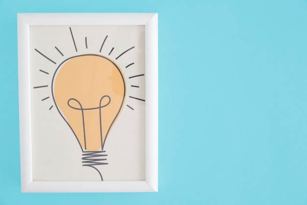 Yellow hand drawn light bulb white frame over blue background