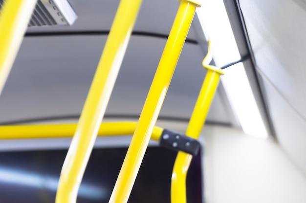 Yellow handle railings inside the bus, passenger transportation.
