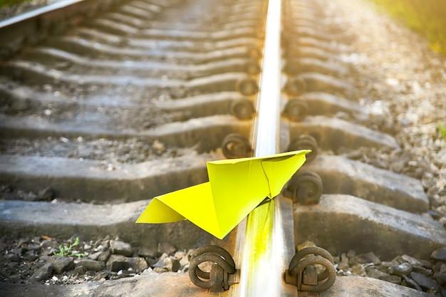 Желтый бумажный самолетик ручной работы, лежащий на рельсовых путях. фото концепции свободы. мотивация образа жизни путешествия. отрасль железнодорожного транспорта.