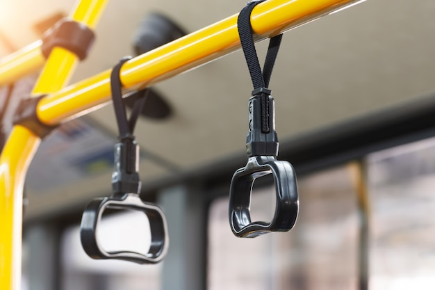 Yellow handrails and black handles to hold passengers steady while the bus is moving.