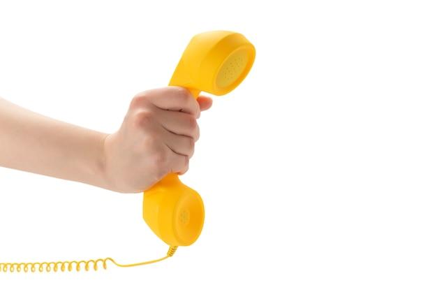 Желтый телефон в руке женщины, изолированные на белом фоне