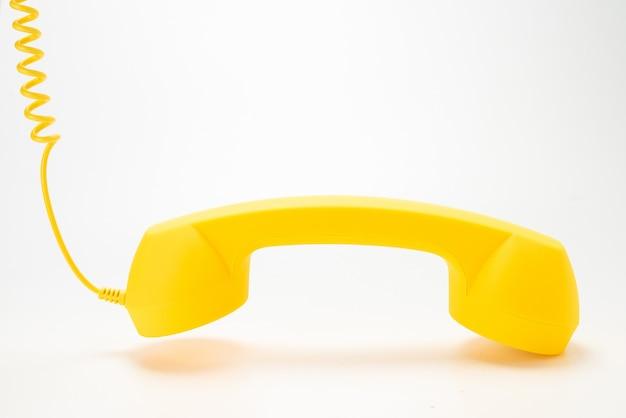 Желтая телефонная трубка изолированная на белизне.