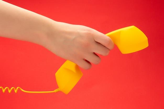 女性の手で赤い背景に黄色の携帯電話。スペースをコピーします。