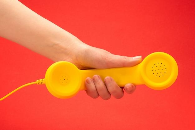 Желтый телефон на красном фоне в руке женщины.