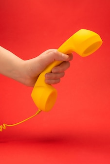 Желтая телефонная трубка на красном цвете в руке женщины.