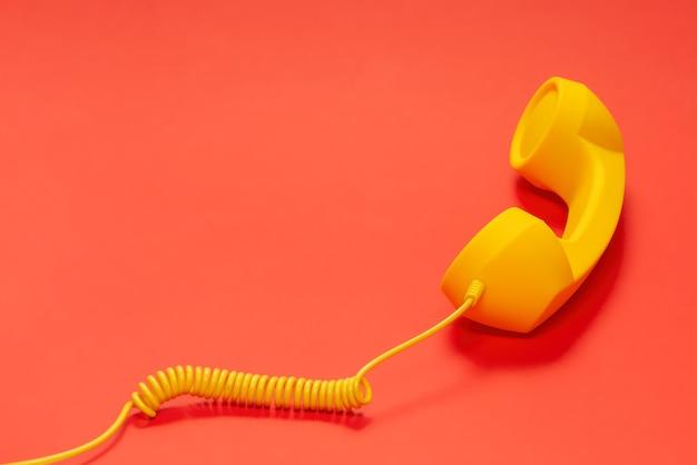 빨간색 표면에 노란색 핸드셋입니다. 공간을 복사합니다.
