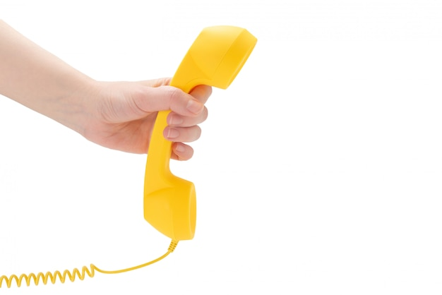Yellow handset in woman hand isolated on white.