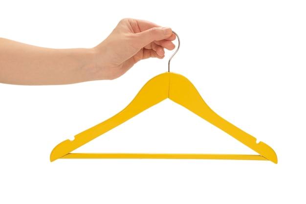 Желтая вешалка в руке женщины изолированная на белизне.