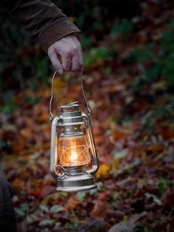 Желтый подвесной фонарь в руке ночью. закройте вверх.