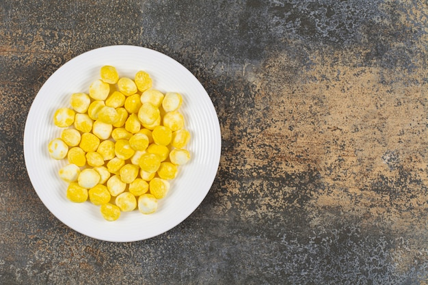 Yellow hard candies on white plate.