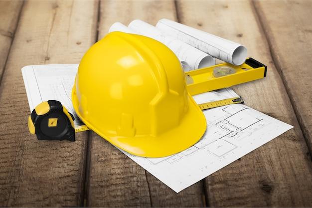建設コンセプトの木製の机の上の黄色いヘルメットと青写真