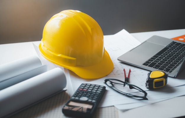 Yellow hard hat safety helmet on a work desk with a design plan of the house