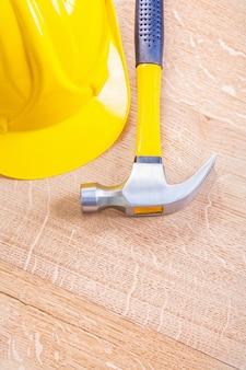 ヴィンテージ木製ボードコピースペース建設コンセプト背景垂直バージョンの黄色いヘルメットとクローハンマー