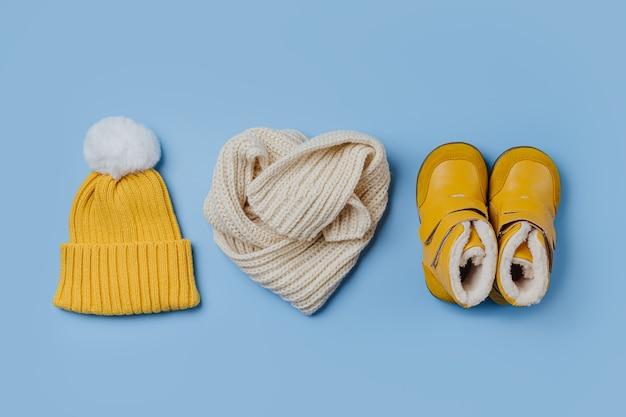 파란색 배경에 스카프가 달린 노란색 모자와 부츠. 스타일리시한 아동복. 겨울 패션 복장