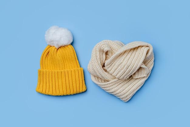 파란색 배경에 노란색 모자와 스카프입니다. 스타일리시한 아동복. 겨울 패션 복장