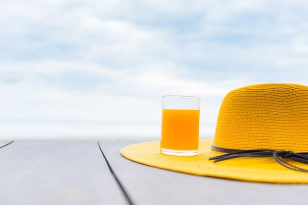 ビーチで新鮮なオレンジジュースと黄色い帽子。青い空を背景にスペースのある夏休み。