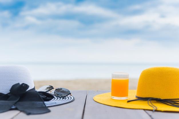 Желтая шляпа со свежим апельсиновым соком на пляже. летние каникулы с космосом на фоне голубого неба.
