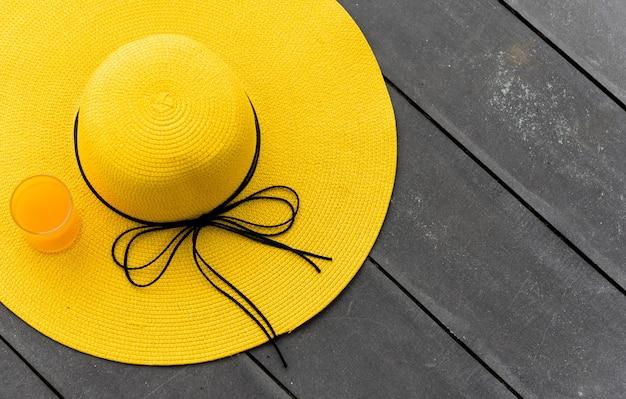 Желтая шляпа со свежим апельсиновым соком на пляже. летние каникулы с космосом на деревянной предпосылке.