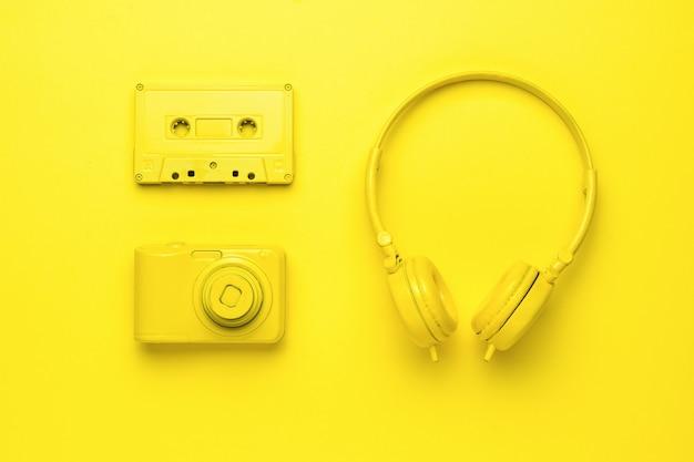 Желтые наушники, фотоаппарат и магнитофон на желтом фоне. монохромное изображение творческих аксессуаров. творческий образ.