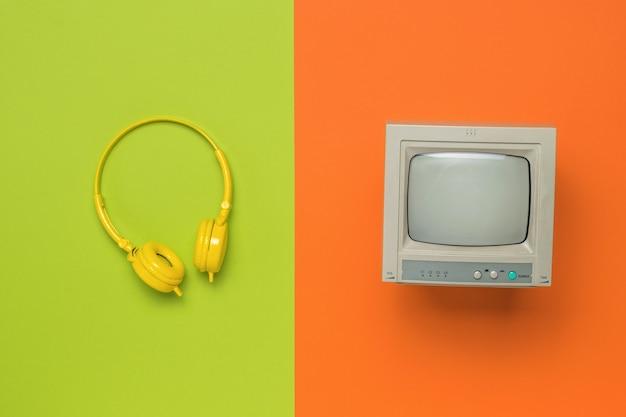 노란색 헤드폰과 녹색 및 주황색 배경에 회색 모니터. 플랫 레이.