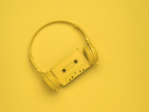 노란색 헤드폰과 노란색 배경에 자기 테이프가 있는 노란색 카세트. 컬러 트렌드. 음악을 듣기 위한 빈티지 장비입니다. 플랫 레이.