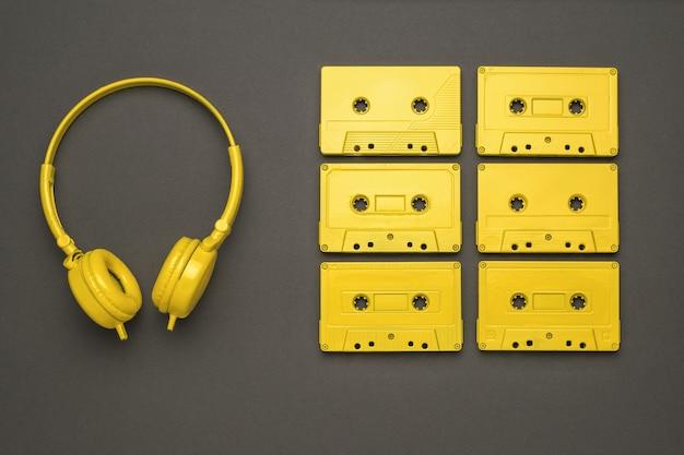 노란색 헤드폰과 검정색 배경에 깔끔하게 쌓인 테이프 카세트 6개. 컬러 트렌드. 음악을 듣기 위한 빈티지 장비입니다. 플랫 레이.