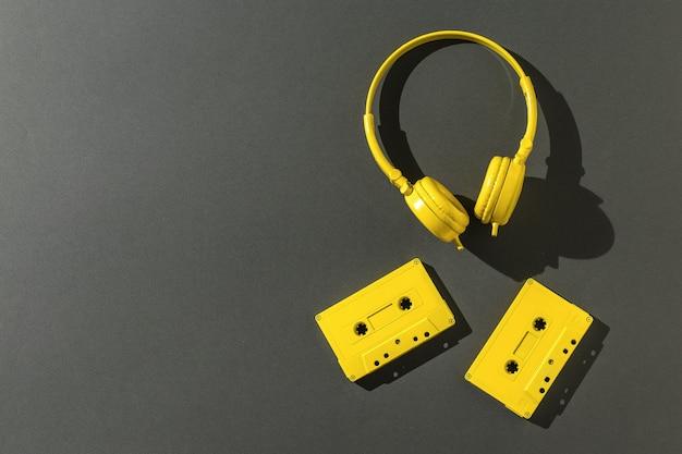 검정색 배경에 밝은 빛에 노란색 헤드폰과 두 개의 테이프 카세트. 텍스트를 위한 공간입니다. 컬러 트렌드. 플랫 레이.