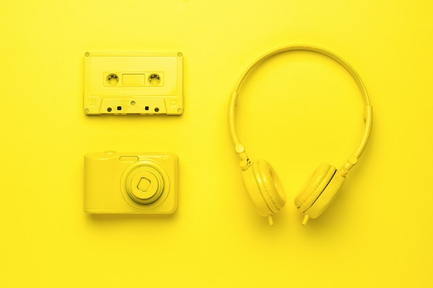 Yellow headphones, a camera and a tape recorder on a yellow background. monochrome image of creative accessories. creative image.