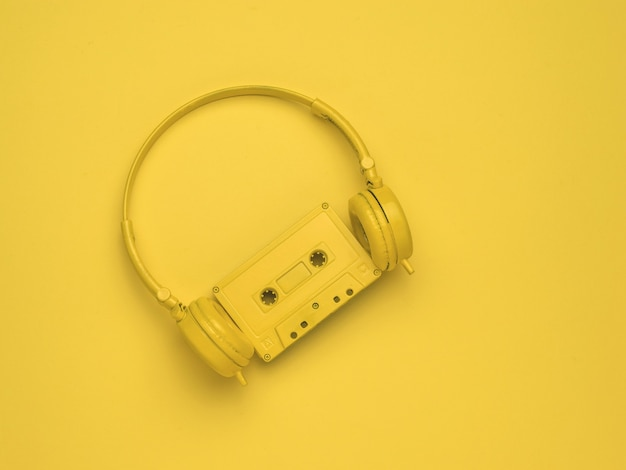 Yellow headphones and a yellow cassette with a magnetic tape on a yellow background. color trend. vintage equipment for listening to music. flat lay.