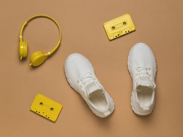 베이지색 배경에 노란색 헤드폰, 노란색 테이프 카세트, 흰색 운동화. 스포츠 스타일입니다. 플랫 레이.