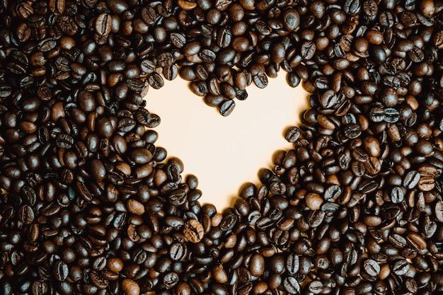 黄色いハートはたくさんのコーヒーの穀物の中に描く