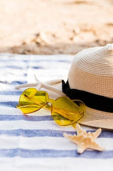 黄色の心臓サングラス、藁の帽子、ビーチでビーチタオルにヒトデ