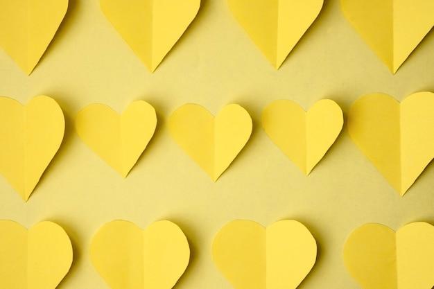黄色の背景、上面図の色紙から切り取られた黄色のハート。モノクロ色のバレンタインデーのコンセプト。