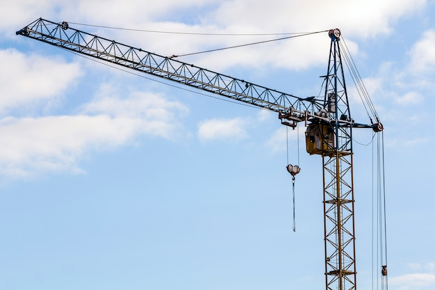 Yellow heavy duty industrial tower construction crane against blue sky with copy space