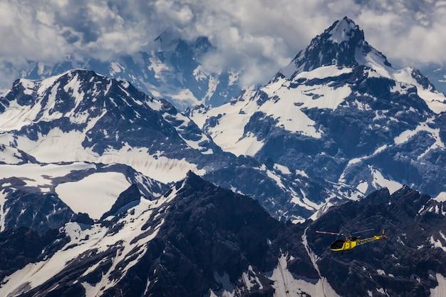 コーカサスの黄色いヘリコプターと雪をかぶった山々