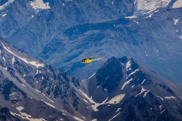 A yellow helicopter on a background of mountains