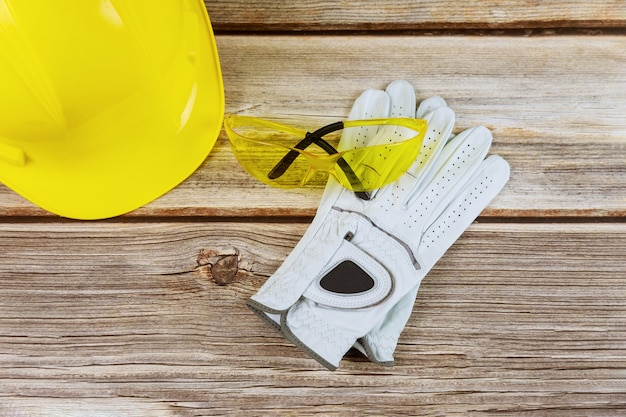 Yellow helmet in construction, protective gloves, glasses on wooden background