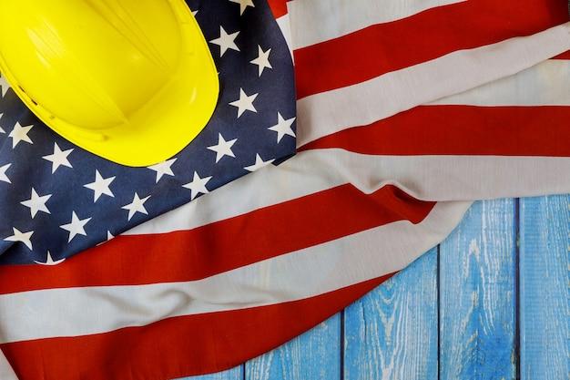 木製の背景に黄色いヘルメットハッピー労働者の日アメリカの愛国心が強いアメリカの国旗