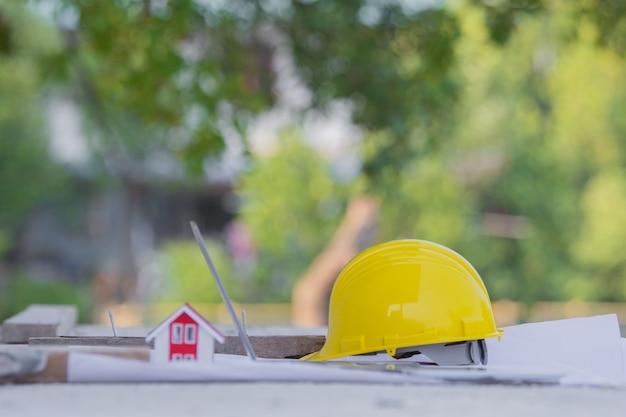 Желтый шлем безопасности каски при строительстве площадки для недвижимости