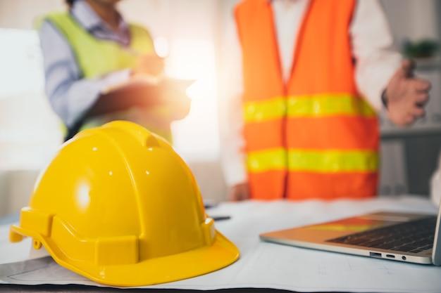 Желтый шлем строителя на столе для совещаний