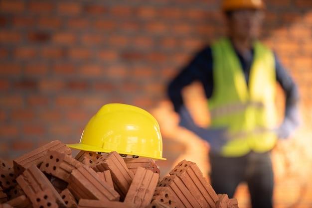 黄色いヘルメットがレンガの山またはオレンジ色の粘土でできたレンガの上に置かれました。建物の背景素材は建設現場です。