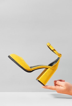 Yellow high-heeled suede shoe balancing on the finger of female hand.