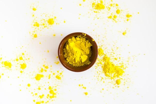 Желтый холи цветной порошок в миске на белом фоне
