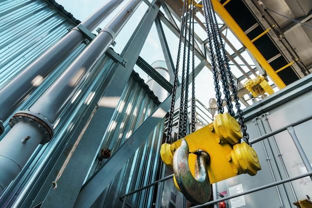 Желтый крюк и цепь заводского мостового крана