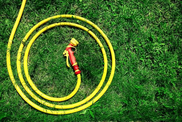 노즐이 있는 노란색 호스는 정원에 고리로 접힌 녹색 잔디에 놓여 있습니다.
