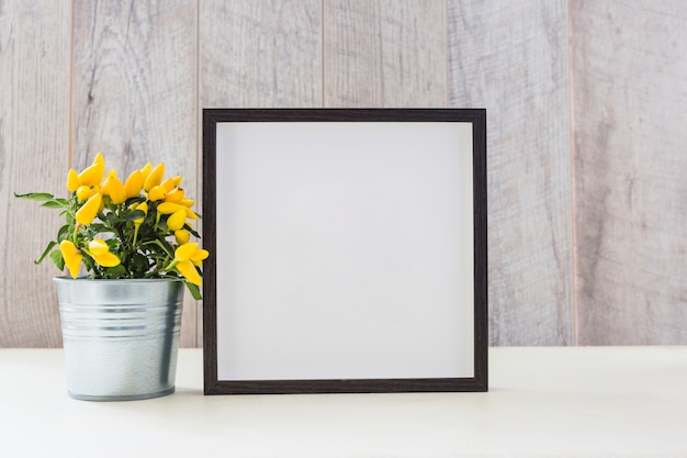 Yellow hot chili peppers in silver pot and white picture frame on table