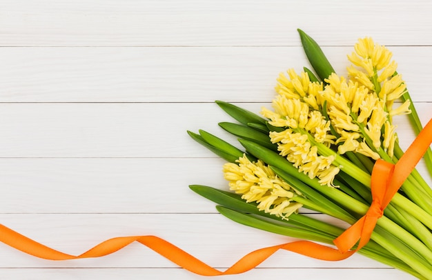 Yellow hyacinths decorated with orange ribbon on white wooden background. top view, copy space