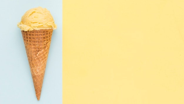 Yellow ice cream in wafer cone on blue and yellow background