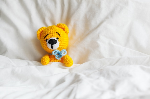 Yellow ill teddy bear lying in bed on white.